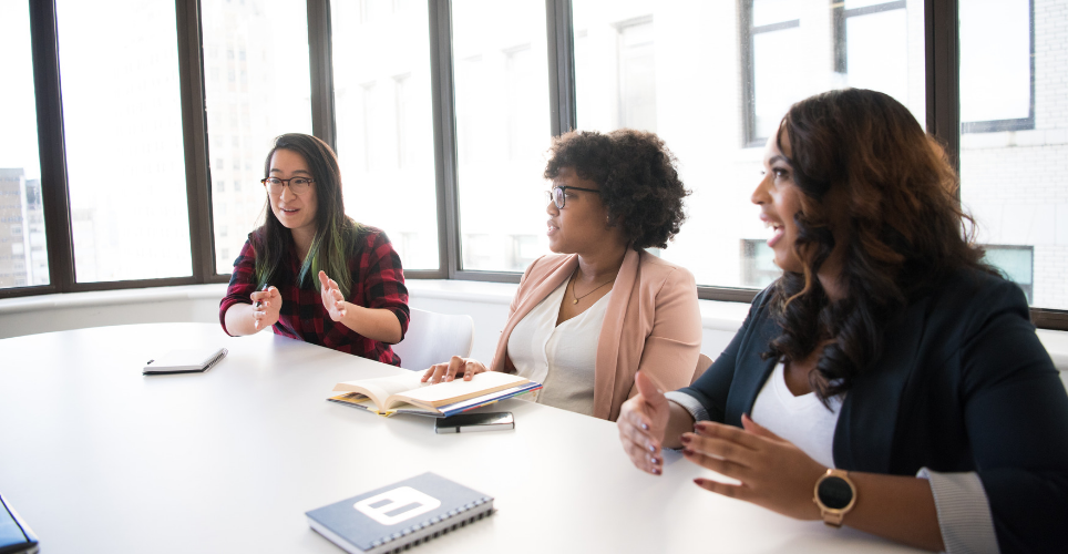 Three women talking at a conference table.