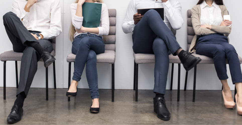 Four job candidates holding resumes waiting to be interviewed