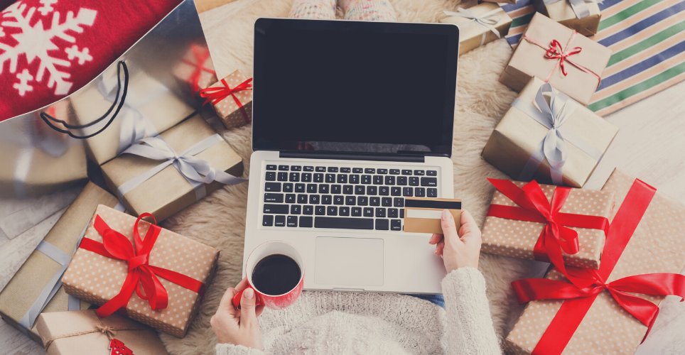 Person surrounded by gifts and holding a credit card in front of a laptop.