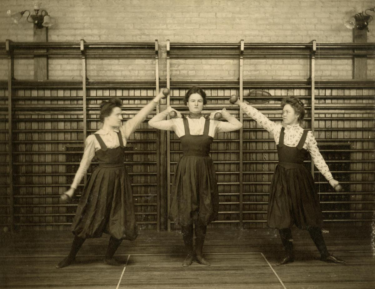 Photo of women lifting weights in a U-M gymnasium, circa 1900. Photo from the University of Michigan Bentley Historical Library.