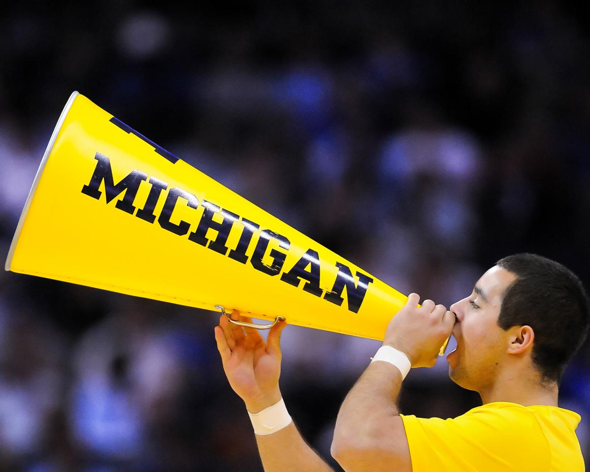 Cheerleader with megaphone at a Michigan game.