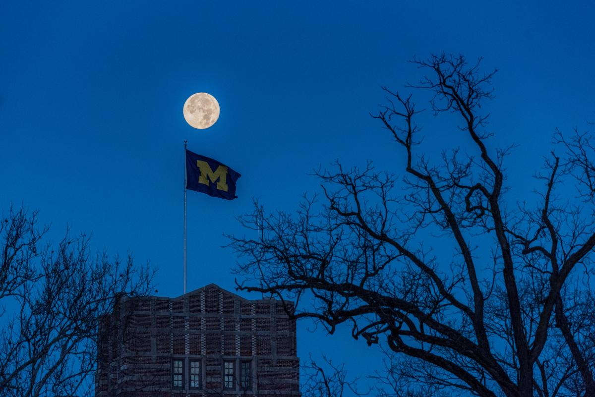 Moonrise above a flag showing the Block M