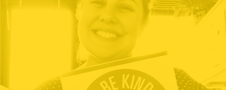 Yellow tined image of woman smiling holding a kindness pledge