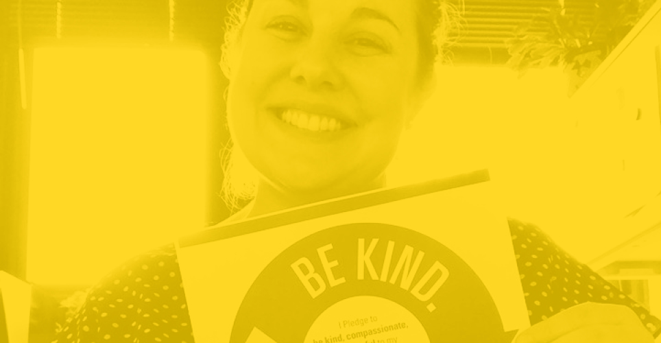 Yellow tinted image of woman smiling holding kindness pledge