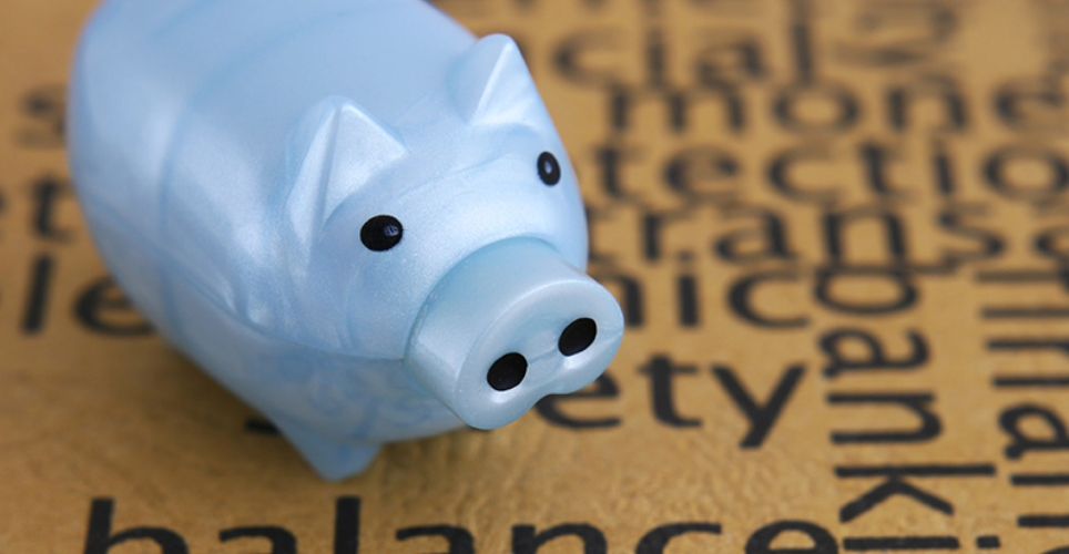 Blue piggy bank on top of financial words