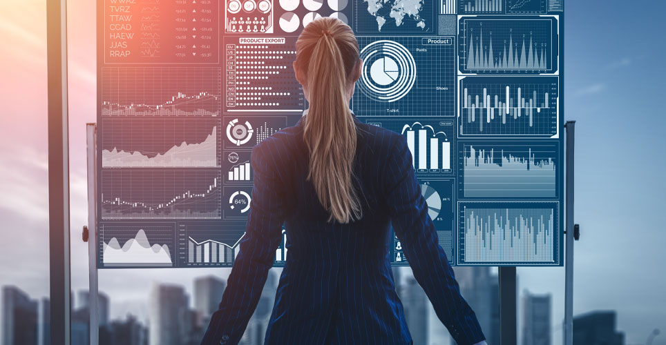 white woman dressed in professional attire with her back to the camera and a data board in her background