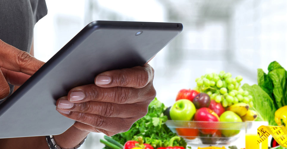 Close up of African-American hand holding a tablet with colorful fruits and veggies in the background.