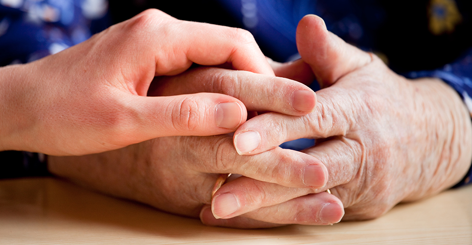 Younger hand comforting older adult