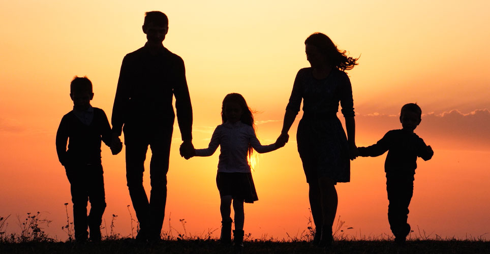 Backlit shot of five people - two adults and three children - holding hands as they walk into a sunset.
