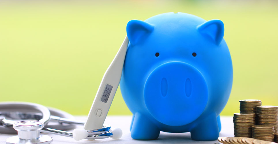 Blue piggy bank next to a thermometer and coins.