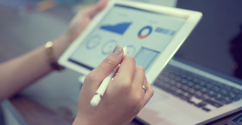 Close up of two hands handling a tablet with financial data showing