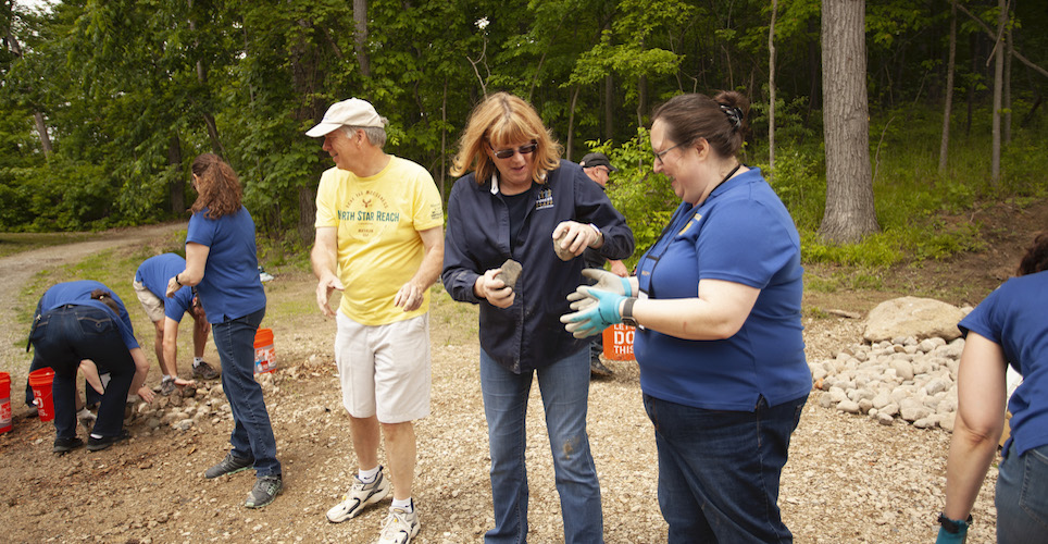 Voices Team members helping to move river rocks at the 2019 annual meeting.