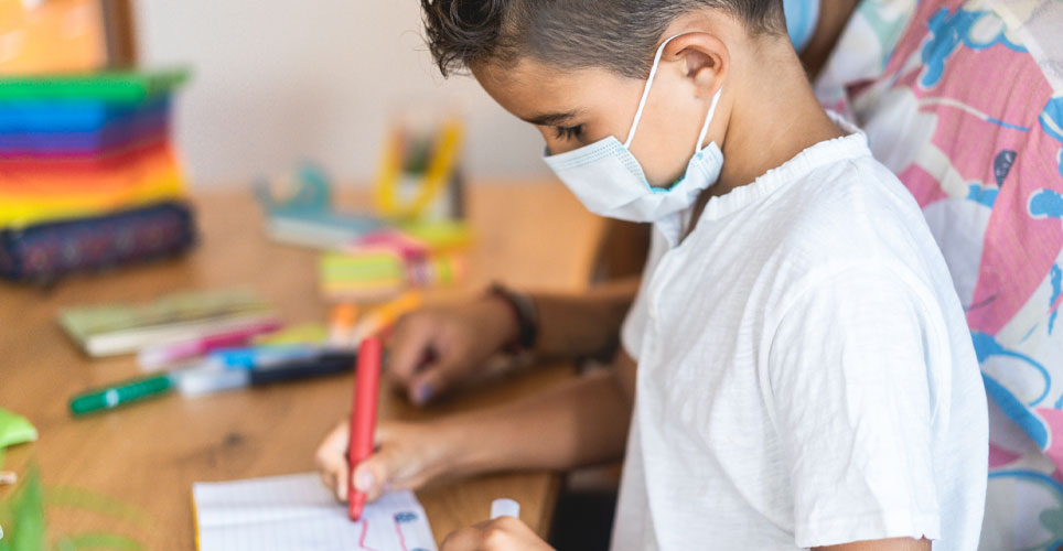 Close up of a child with a face covering, painting in a classroom setting.