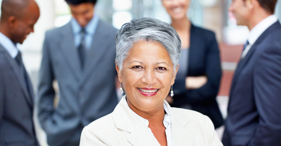 Woman looking into camera with employees looking on behind her