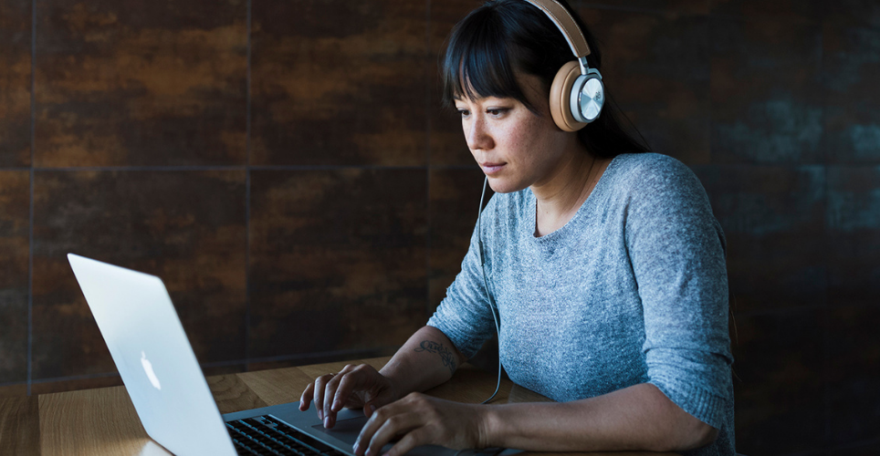 Woman with headphones on, sitting at a desk, typing on a laptop.