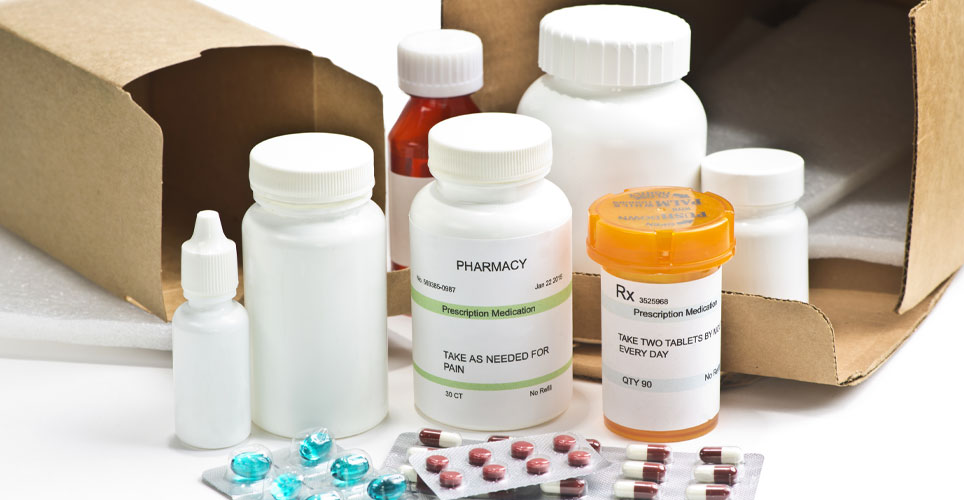 close up of multiple white prescription bottles with open boxes in the background