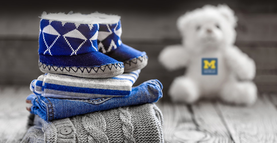 Blue baby booties on pile of baby clothes with white teddy bear