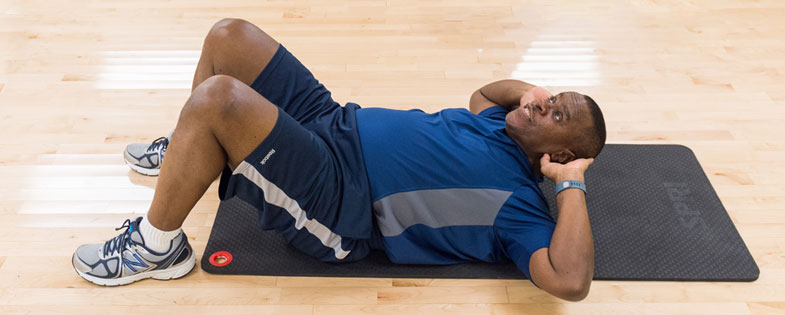 Man performing sit ups in an exercise class