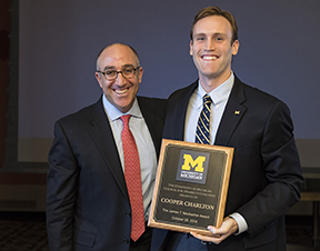 Board of Regents Chair Mark J. Bernstein (left) presents the 27th annual James T. Neubacher Award to Cooper Charlton, co-founder of the Wolverine Support Network, former Central Student Government president, and president of the Student-Athlete Advisory Committee.