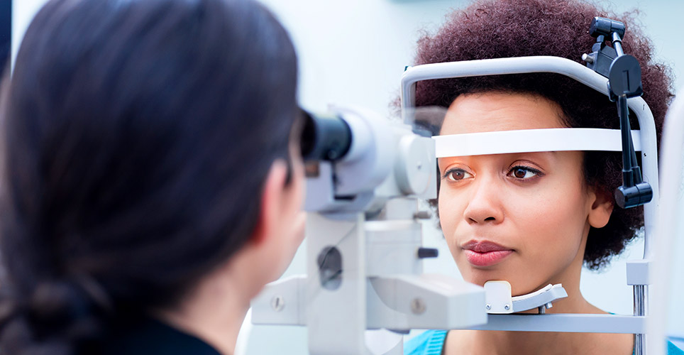 Close up of one woman examining the eye of another woman in an office setting.