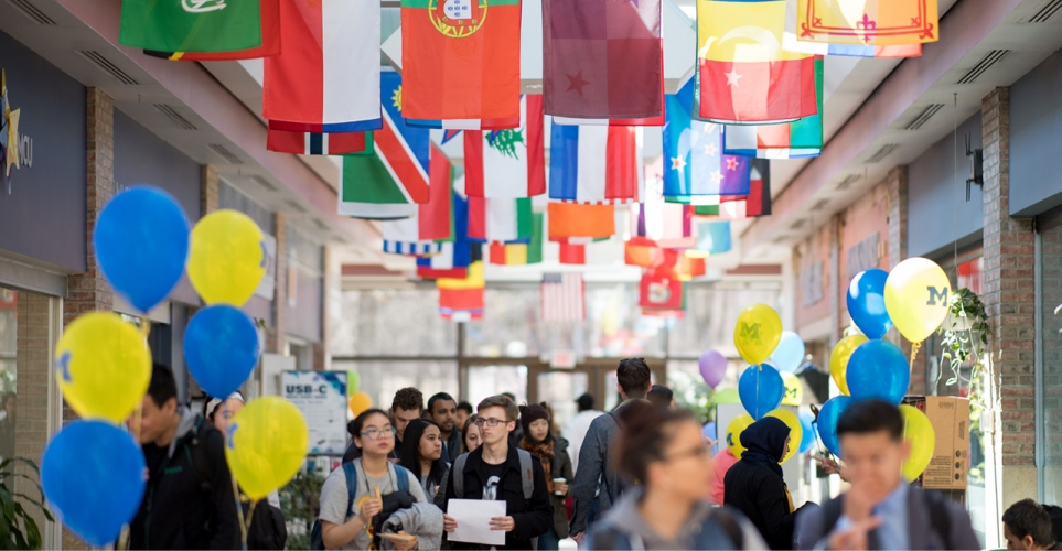 People walking through a hallway with flags from different countries and maize and blue balloons.