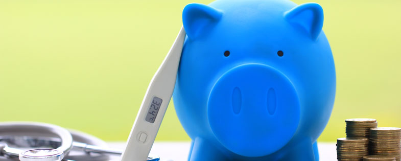 blue piggy bank with thermometer and coins near by.