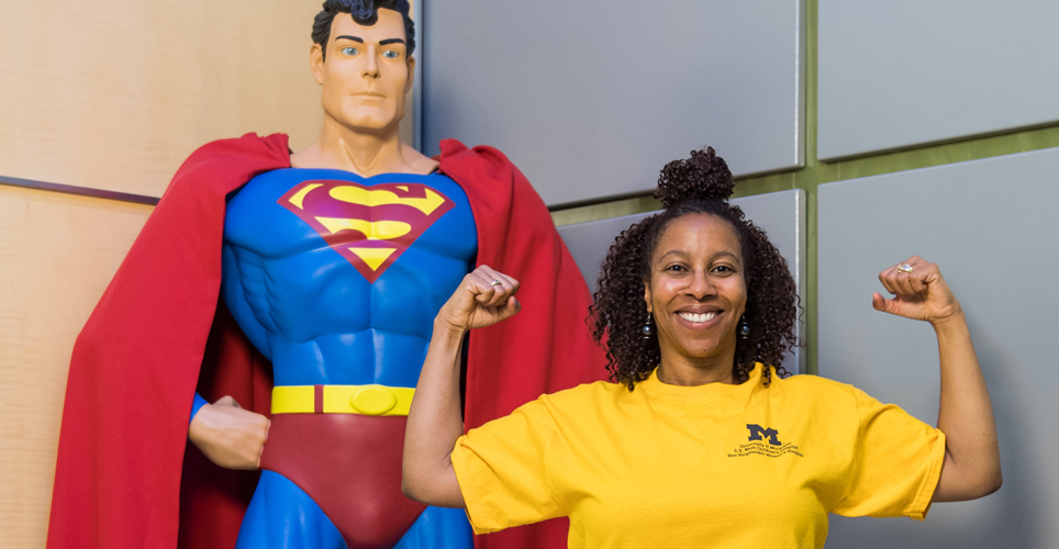 woman holding arms in strong pose with statue of Superman behind her.