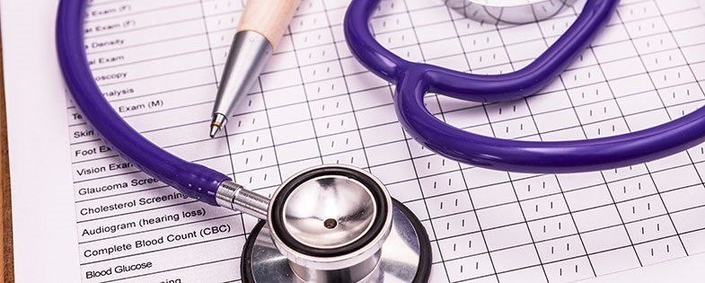 Purple stethoscope and pen on medical paperwork
