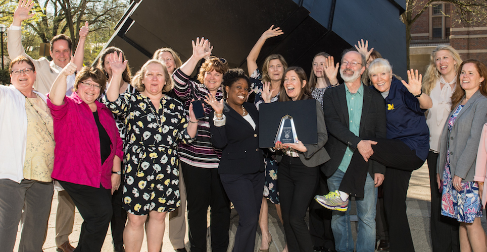The team recipients of the 2018 President's Staff Innovation Award celebrate by the cube.
