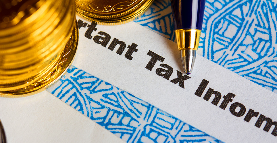 A pen going over the words Important Tax Information on a piece of paper