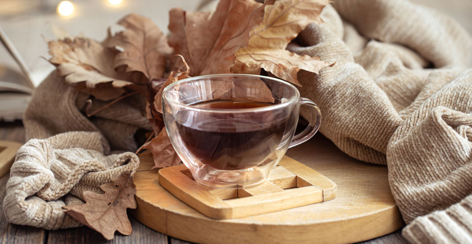 Close up of a clear tea cup filled with tea surrounded by a cream sweater and rust-colored leaves