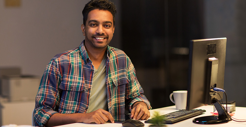 Man smiling while working at computer.