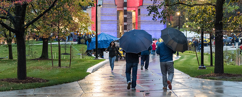 People holding umbrellas and walking in the rain