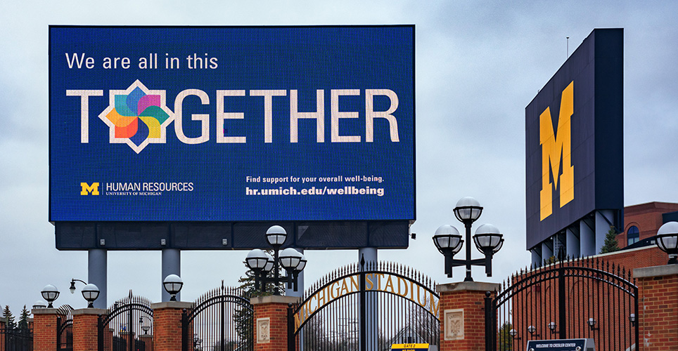 Billboard featuring Michigan's model of well-being outside Michigan Stadium
