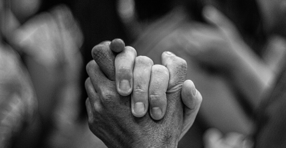 Close up of two hands clasped, suggesting support.
