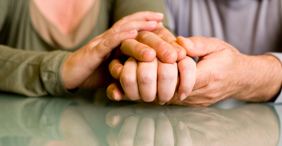 Close up of two people's hands on a table; the hands are entwined.