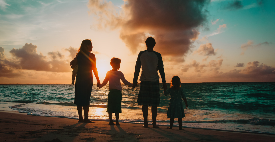 Family holding hands during sunset on a beach