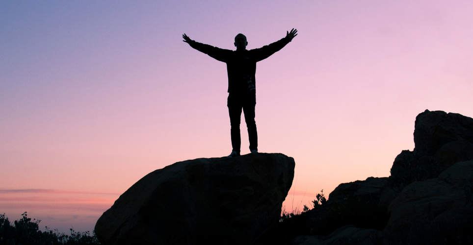 Man standing on rock with arms wide open during a sunset