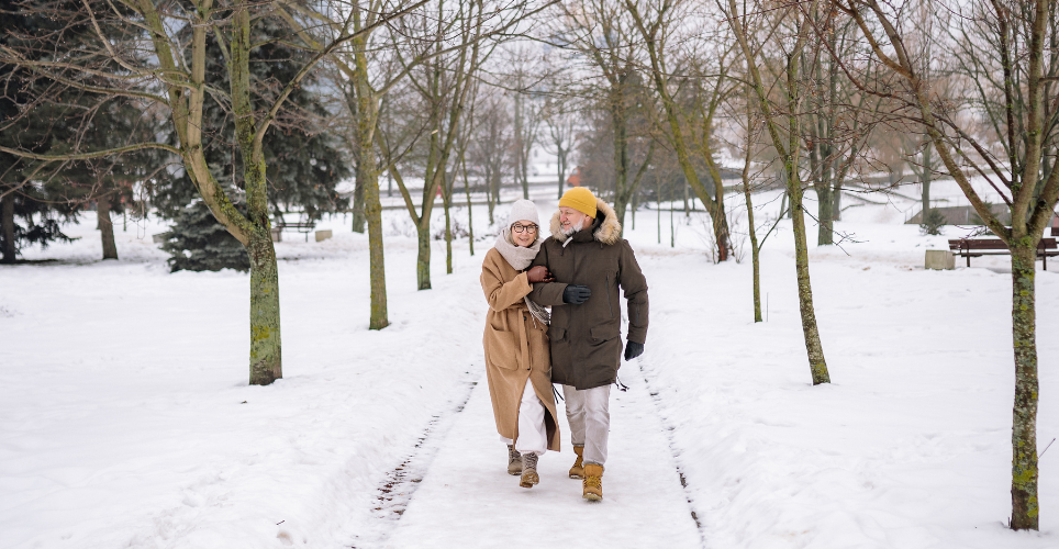 Two close, smiling white seniors walk on a snowy trail in a forest.