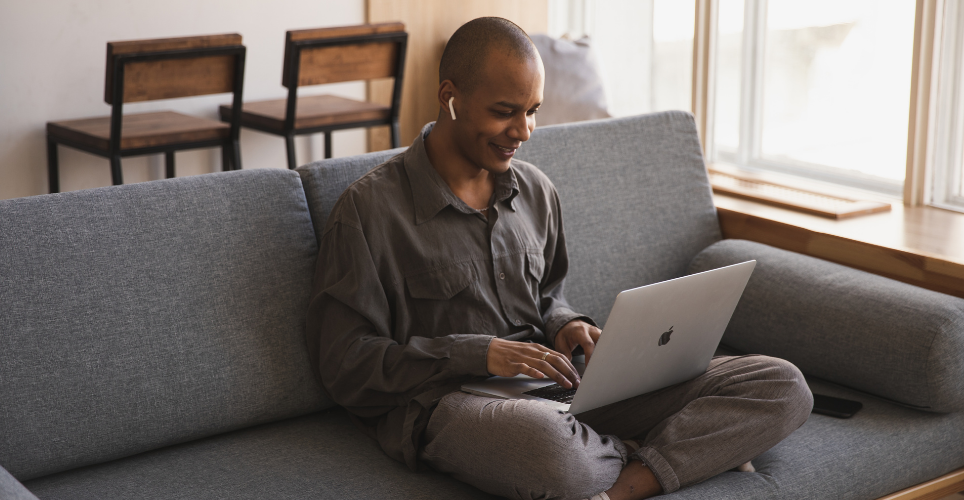Person sitting on couch typing on laptop.