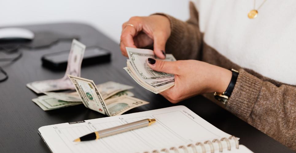 Close up of a women's hands handling paper money with a hand-written ledger near by.