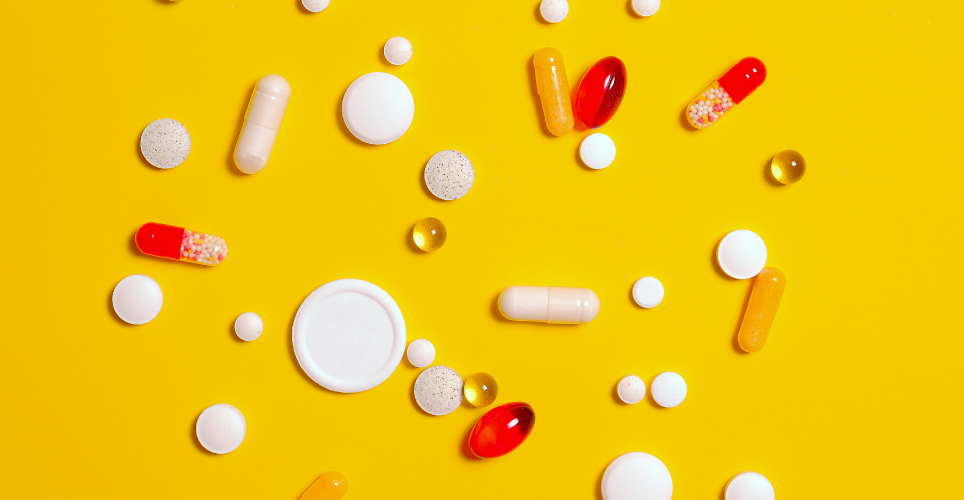 Colorful pills of different shapes on a bright yellow background.