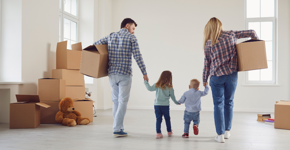 Family of four holding hands and boxes walking through house