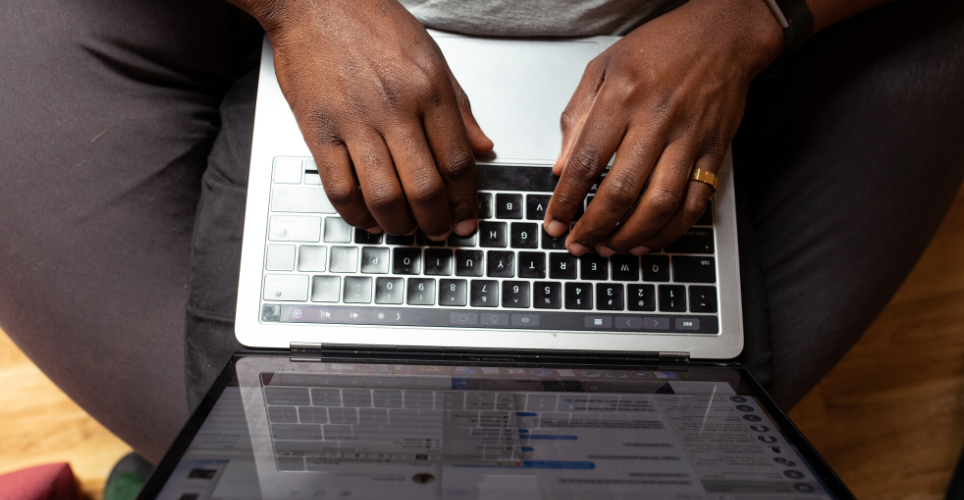 Close up of African-American hands on a black keyboard of a silver lap top.