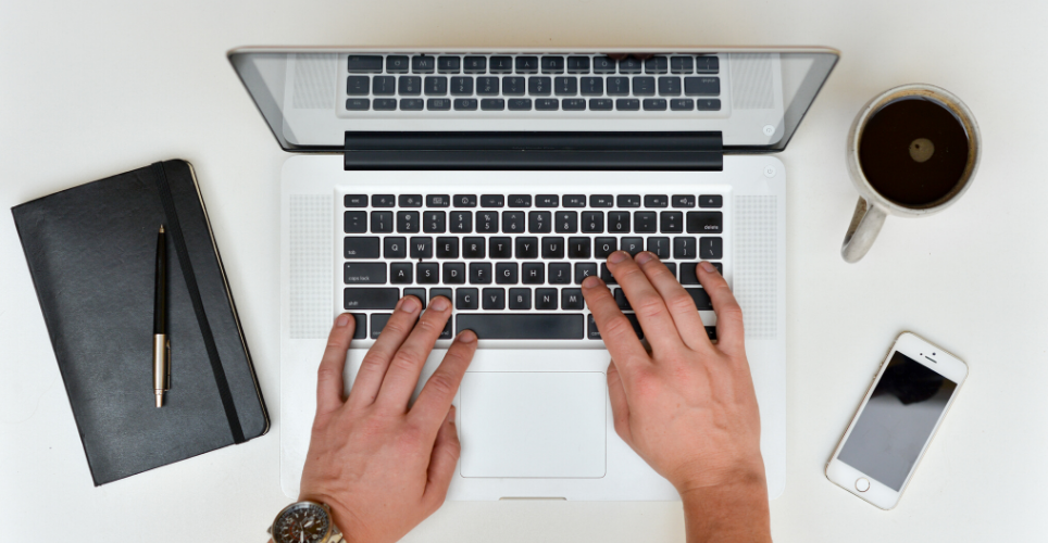 Close up of two hands typing on a lap top keyboard with a cellphone and cup of coffee