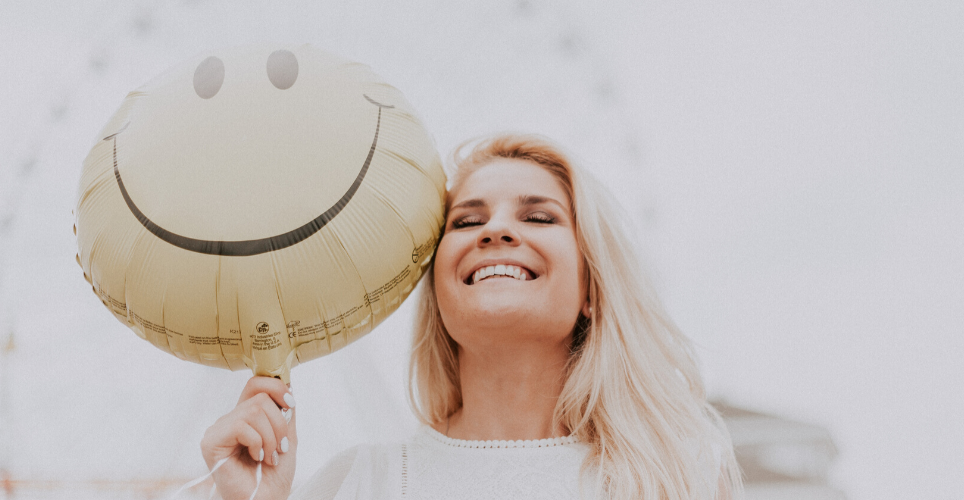 close up of smiling blonde woman holding a smiley-face balloon