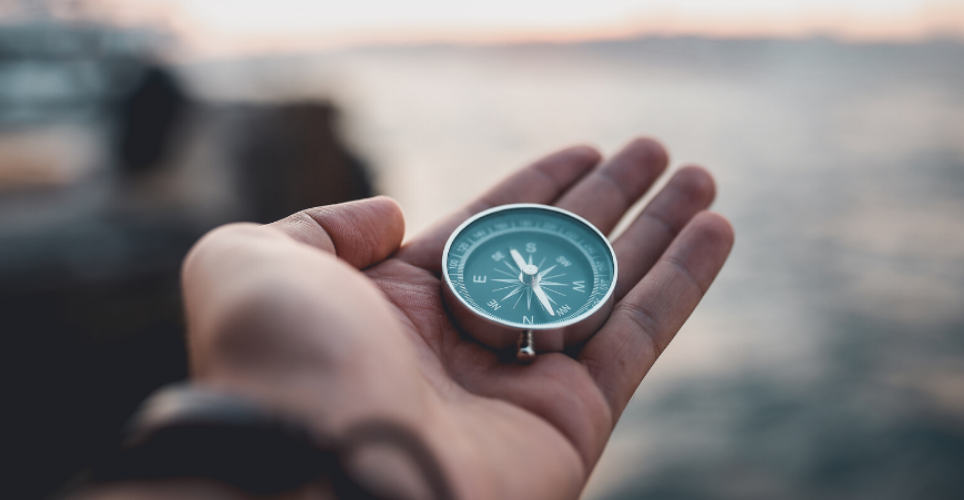 Close up of an open white hand holding a blue compass in the palm.