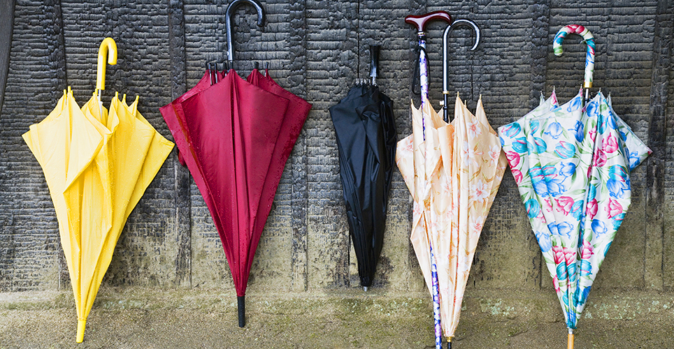 Five multicolored umbrellas leaning on a wall