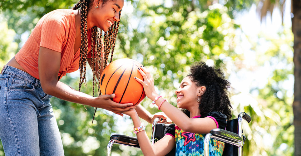 Close of an African-American mom handing a basketball to her daughter who's in a wheelchair