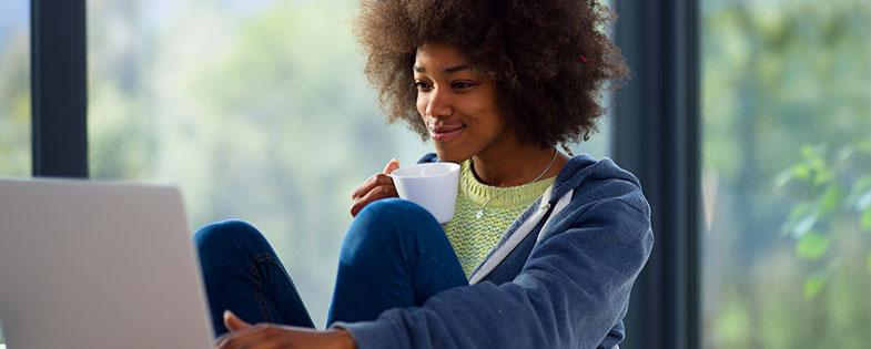 woman on computer drinking tea